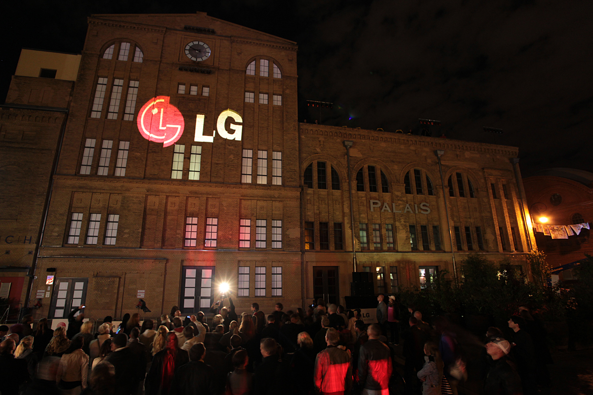 A large audience observes a gigantic 3D LG logo projected onto the front of a building in Kulturbrauerei, Berlin.