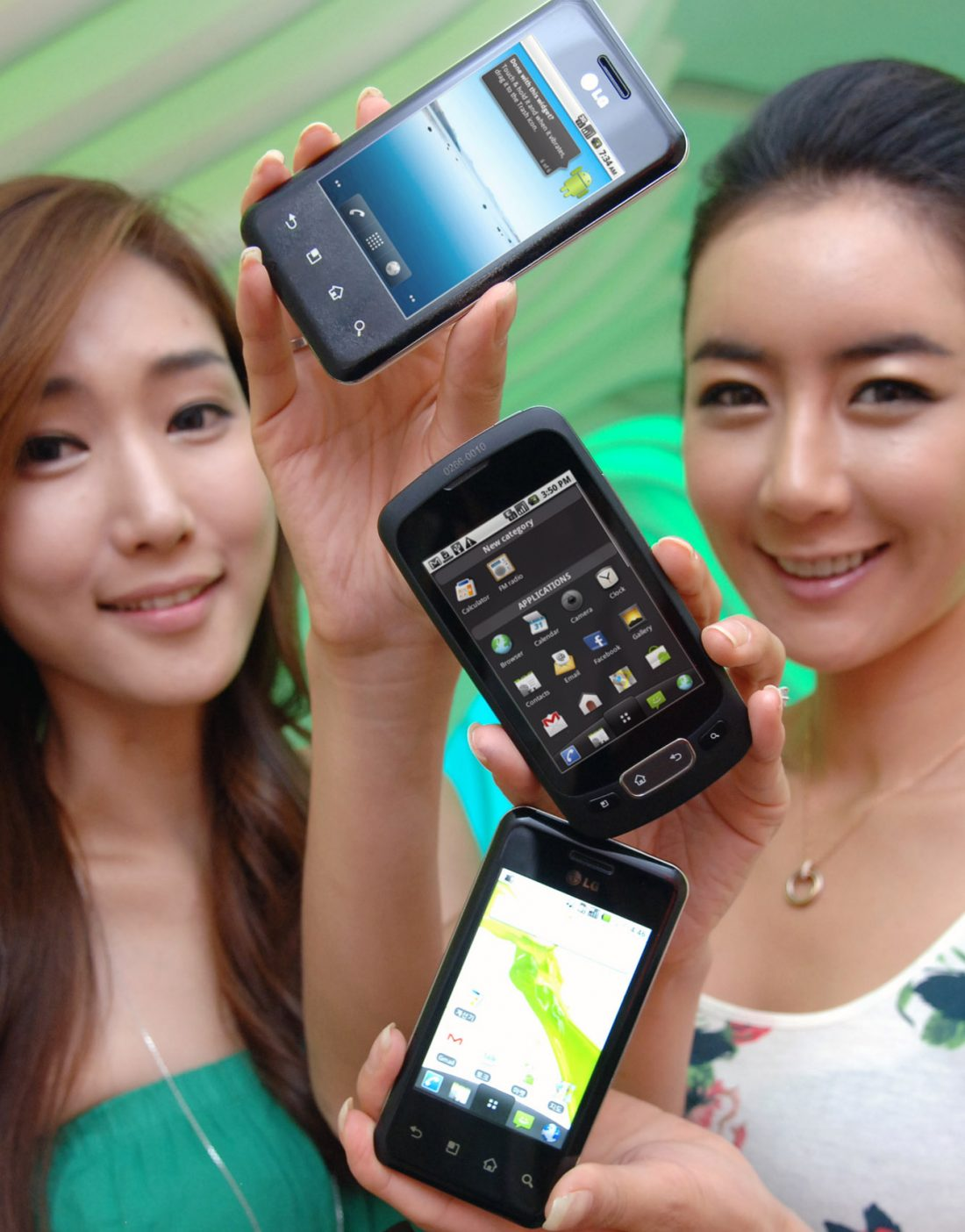 Two models hold up two variants of the LG Optimus Chic and one of the LG Optimus One in a vertical pattern.