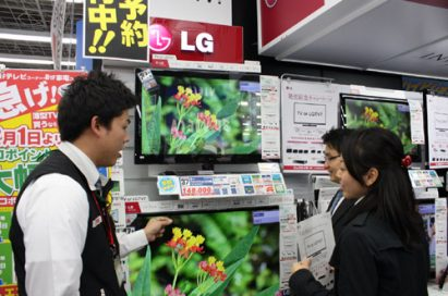 A man explains LG's LED LCD TVs to two visitors at an LG store booth set up in Japan