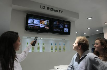 A woman demonstrating the LG EzSign TV to two visitors at ISE 2011