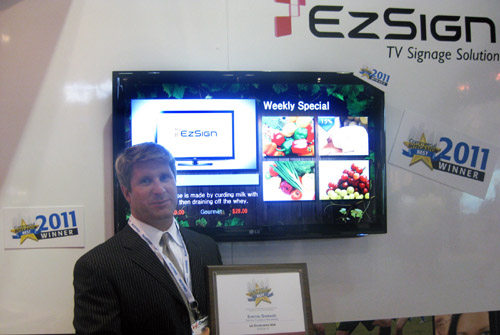 A gentleman holds up a plaque for the BEST Award in front of the LG EZSIGN TV installation at InfoComm 2011.