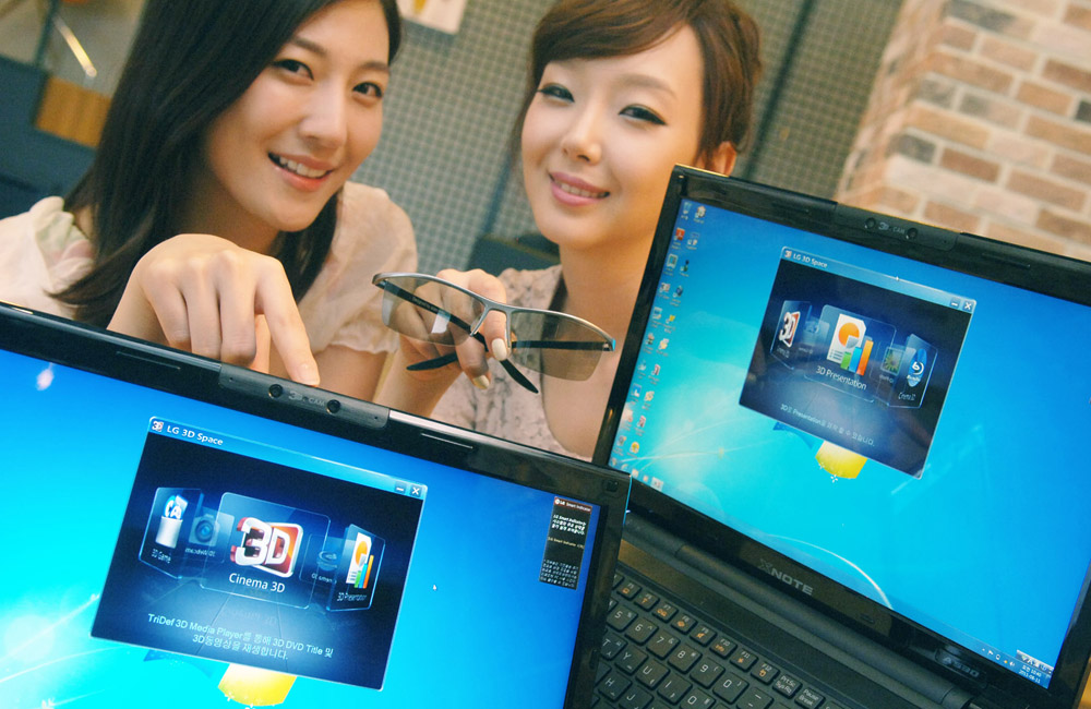 Two female models holding up LG's 3D NOTEBOOKS and a set of 3D glasses