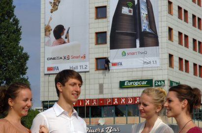 Visitors to IFA 2011 gather in front of a building displaying large advertisements for LG's 3D products