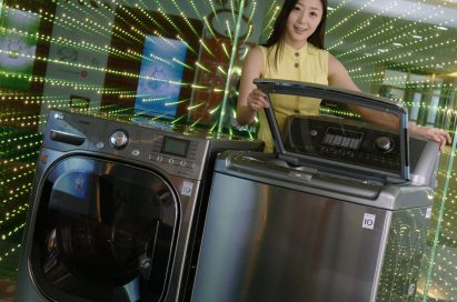 A front view of a woman posing with the LG top-load and front-load washing machines while slightly opening the door of top-loader