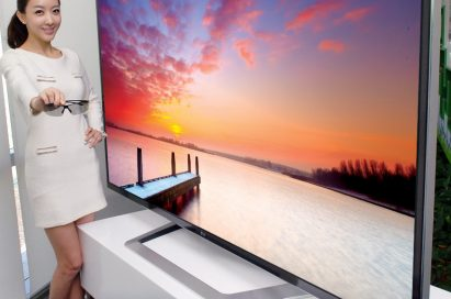 A model holding 3D glasses while showing off the world's largest 84-inch 3D Ultra Definition TV