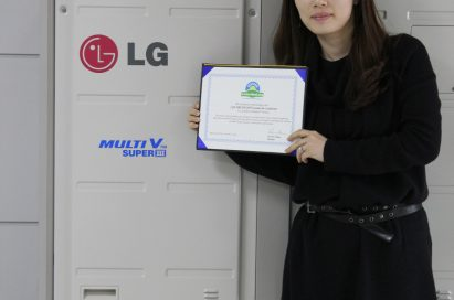 A wider shot of a woman holding up LG MULTI V III's carbon-free certification letter in front of the air conditioner appliance.