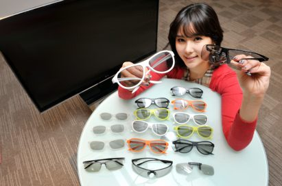 A model presenting the various types and colors of LG's new 3D glasses lineup on a table, with the LG CINEMA 3D TV just behind her