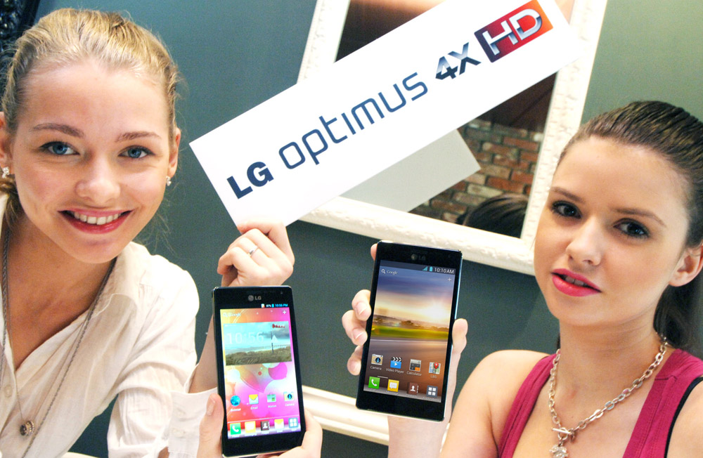 A different-angle photo of two models holding up two LG QUAD-CORE smartphones and a promotional panel engraved with the brand name LG OPTMUS 4X HD