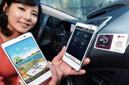 A woman holds two LG Optimus LTE Tags and shows their front views inside a car