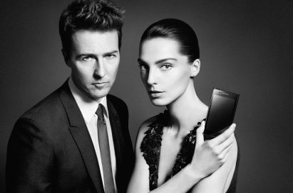 Daria Werbowy holds up the PRADA phone by LG 3.0 showing its front with Edward Norton