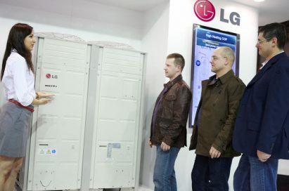 A female attendant explains LG's Multi V HVAC solution to three men at MCE 2012.
