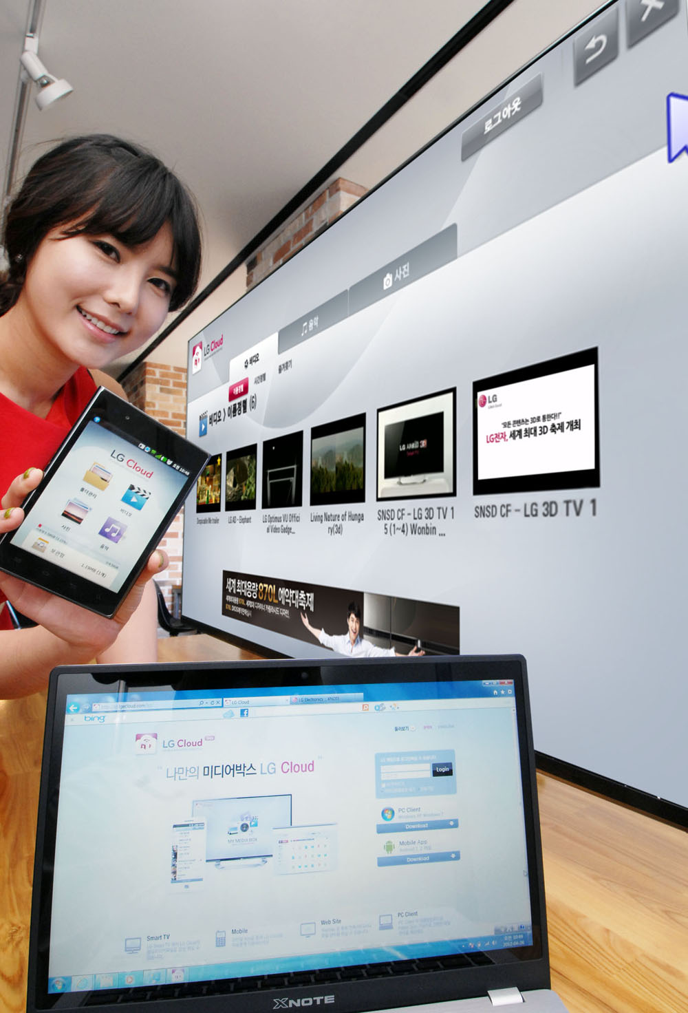 A female model holds up a phone displaying LG Cloud, the company's multimedia cloud platform on the screen while LG's XNote mirrors the phone's screen.