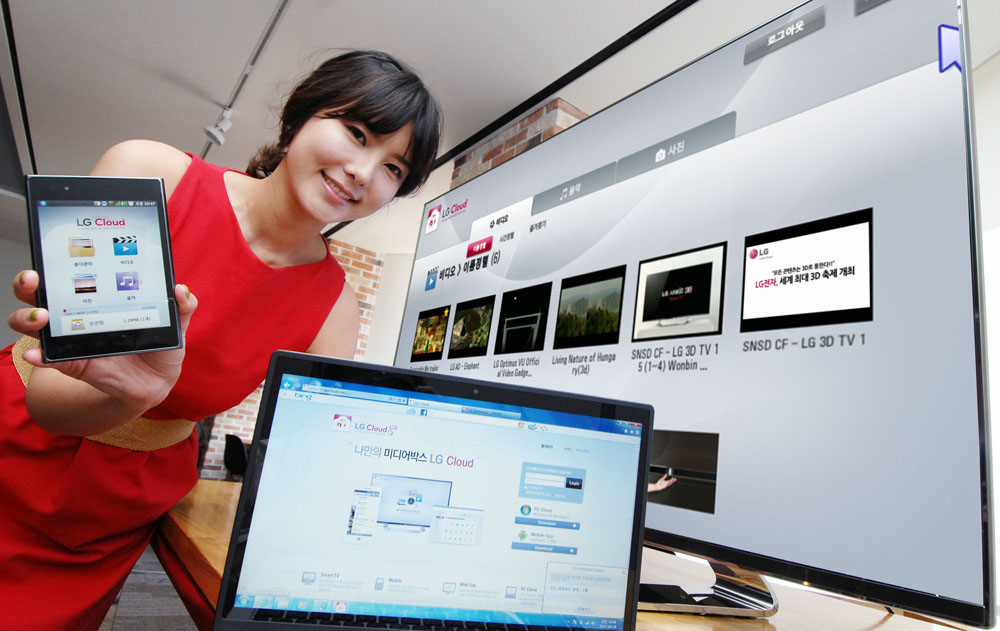 Another view of a female model holding up a phone displaying LG Cloud, the company's multimedia cloud platform on the screen while LG's XNote mirrors the phone's screen