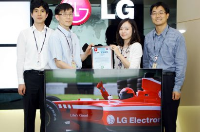 Four LG employees present the Climatop certificate behind LG's CINEMA 3D Smart TV model 47LM760S