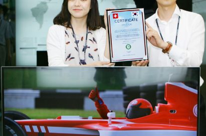 Two LG employees hold up the Climatop certificate behind the company's CINEMA 3D Smart TV model 47LM760S