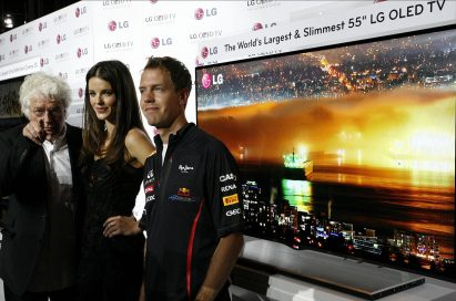 Film director Jean-Jacques Annaud, model Gemma Sanderson and F1 Champion Sebastian Vettel pose in front of LG's new 55-inch OLED TV in Monaco