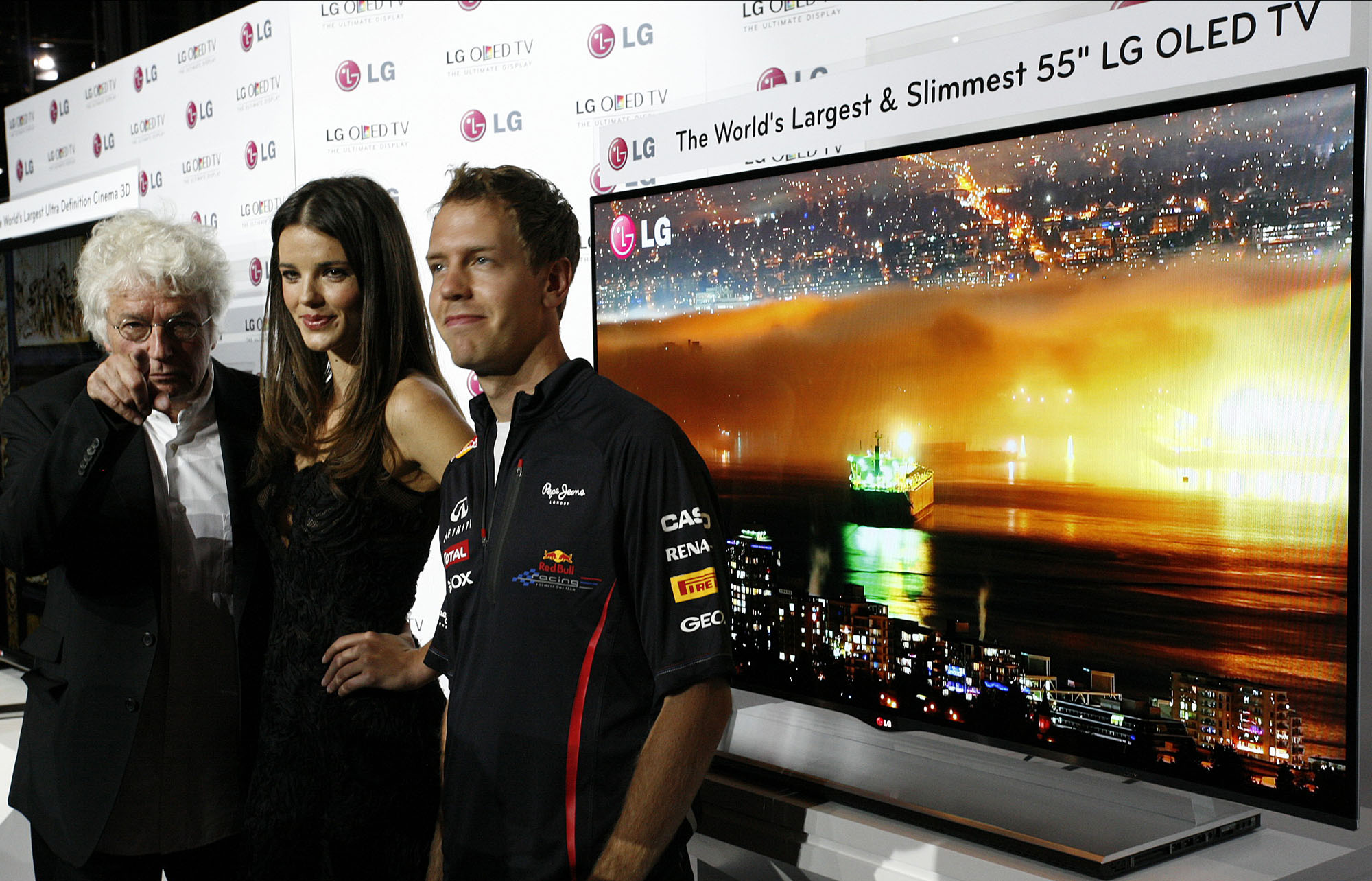 Film director Jean-Jacques Annaud, model Gemma Sanderson and F1 Champion Sebastian Vettel pose in front of LG's new 55-inch OLED TV in Monaco.