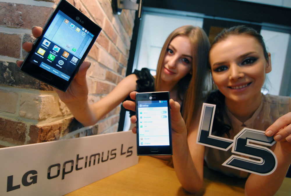 Two women each holding a stylish LG OPTIMUS L5