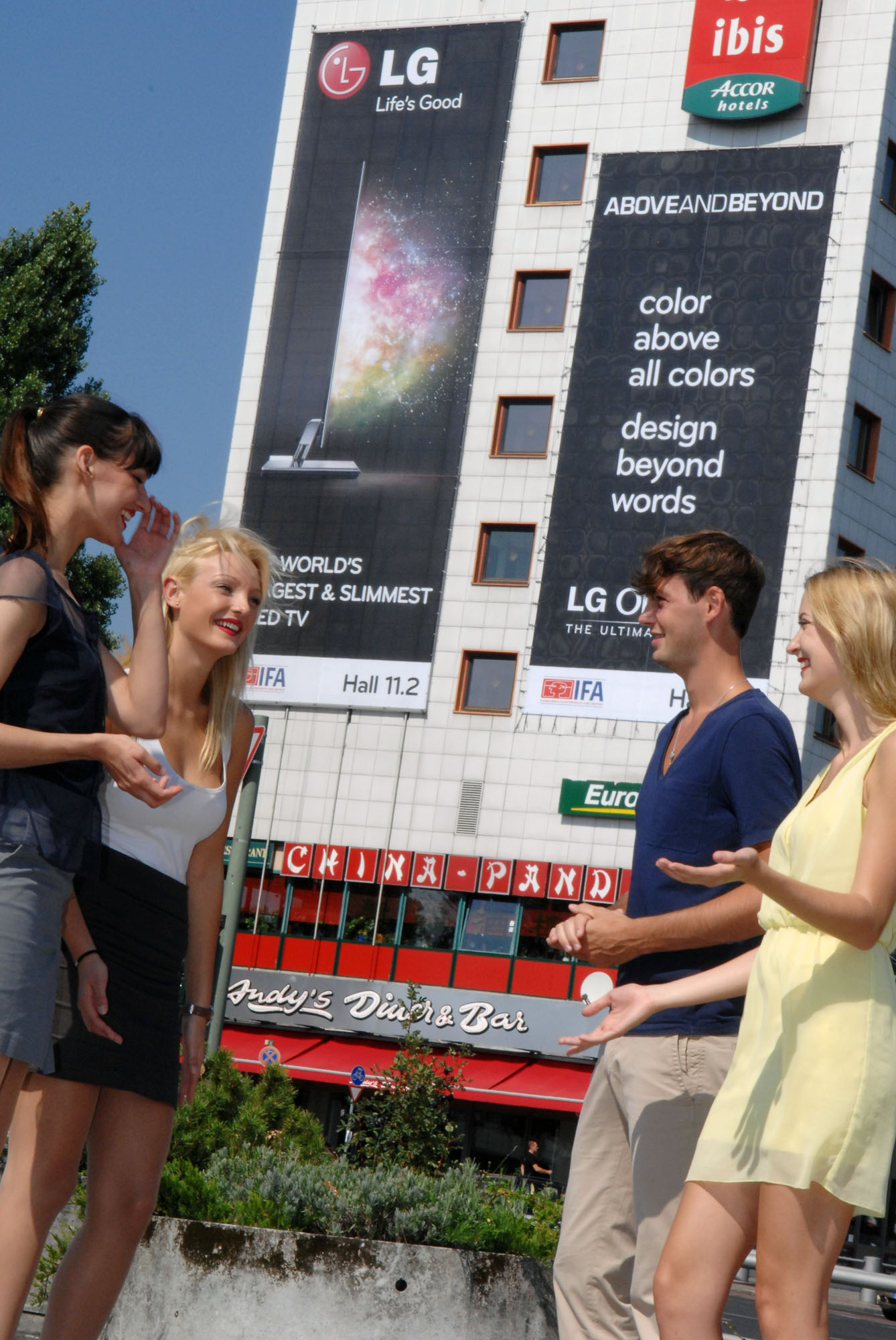 Visitors of IFA 2011 gather in front of a building, the front side of which is covered with outdoor advertisements for LG OLED TV