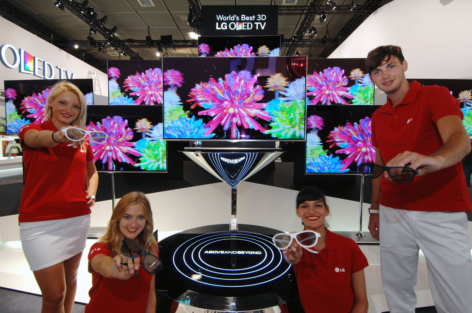 LG booth staff holding 3D glasses while presenting LG's 3D OLED TVs at IFA 2012
