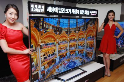 A side view of two models presenting the world's first 84-inch Ultra Definition 3D TV by LG
