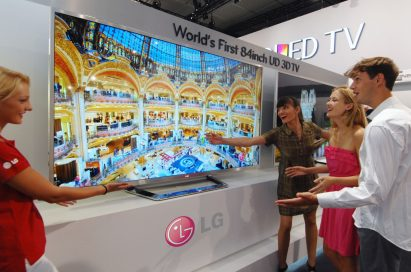 An LG booth staff member introducing the world's first 84-inch UD 3D TV to visitors at IFA 2012