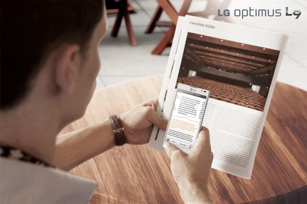 A man uses the LG OPTIMUS L9 phone to look up something in a magazine.