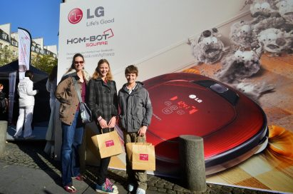 Three visitors pose in front of the LG HOM-BOT advertisement wall