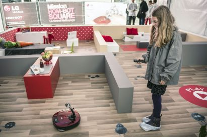 A lady controlling an LG HOM-BOT with its remote control at the LG HOM-BOT SQUARE launch event in France