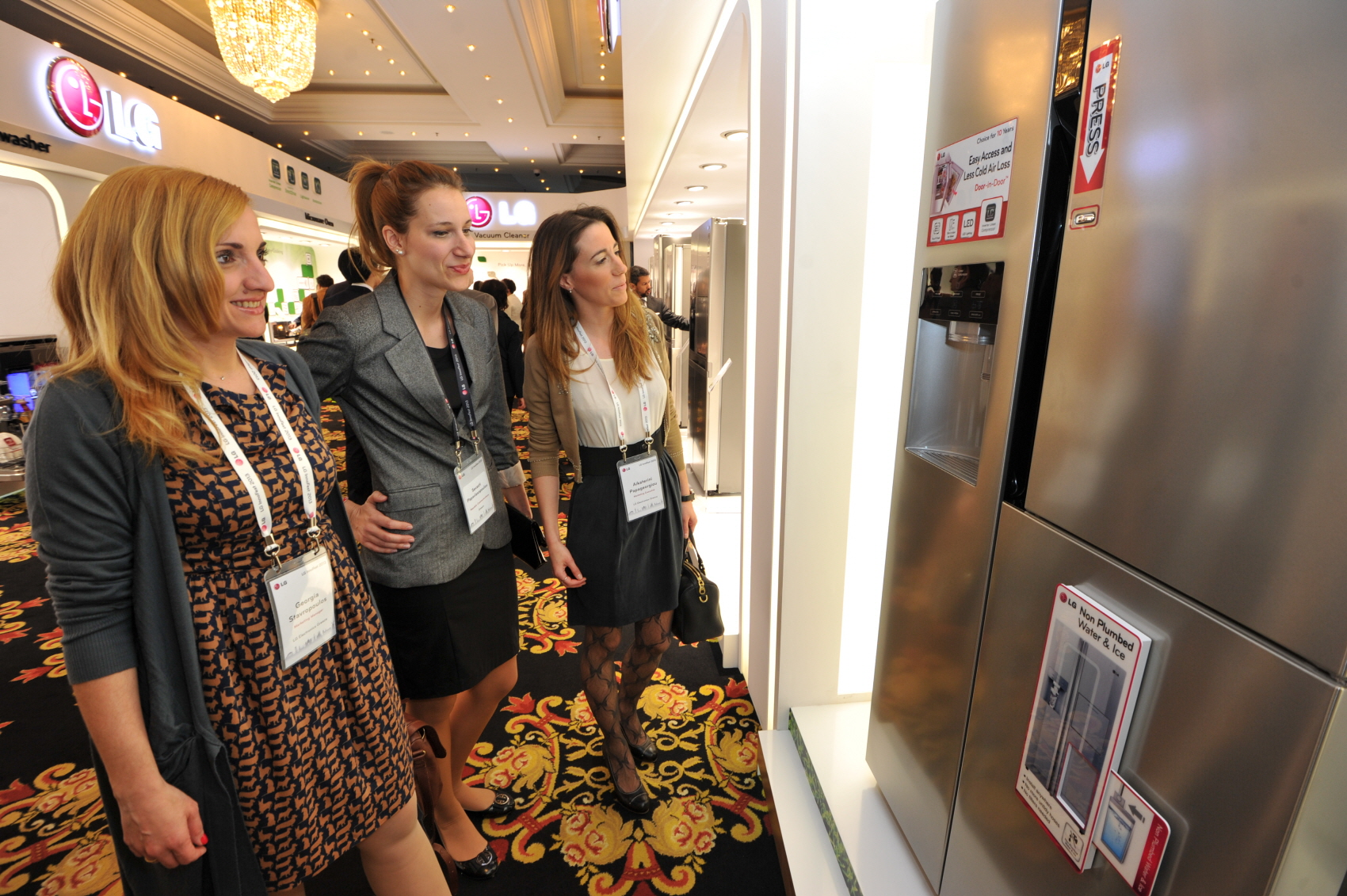 Three visitors observe an LG refrigerator with the Door-in-Door feature