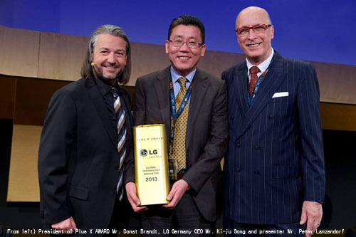 """Song Ki-ju, CEO of LG Electronics Germany, holds the """"Global Technology Innovator 2013"""" award while Donat Brandt, president of Plus X Award, and a presenter Peter Lanzendorf, stand next to him at the Plus X Award Night in Cologne, Germany"""