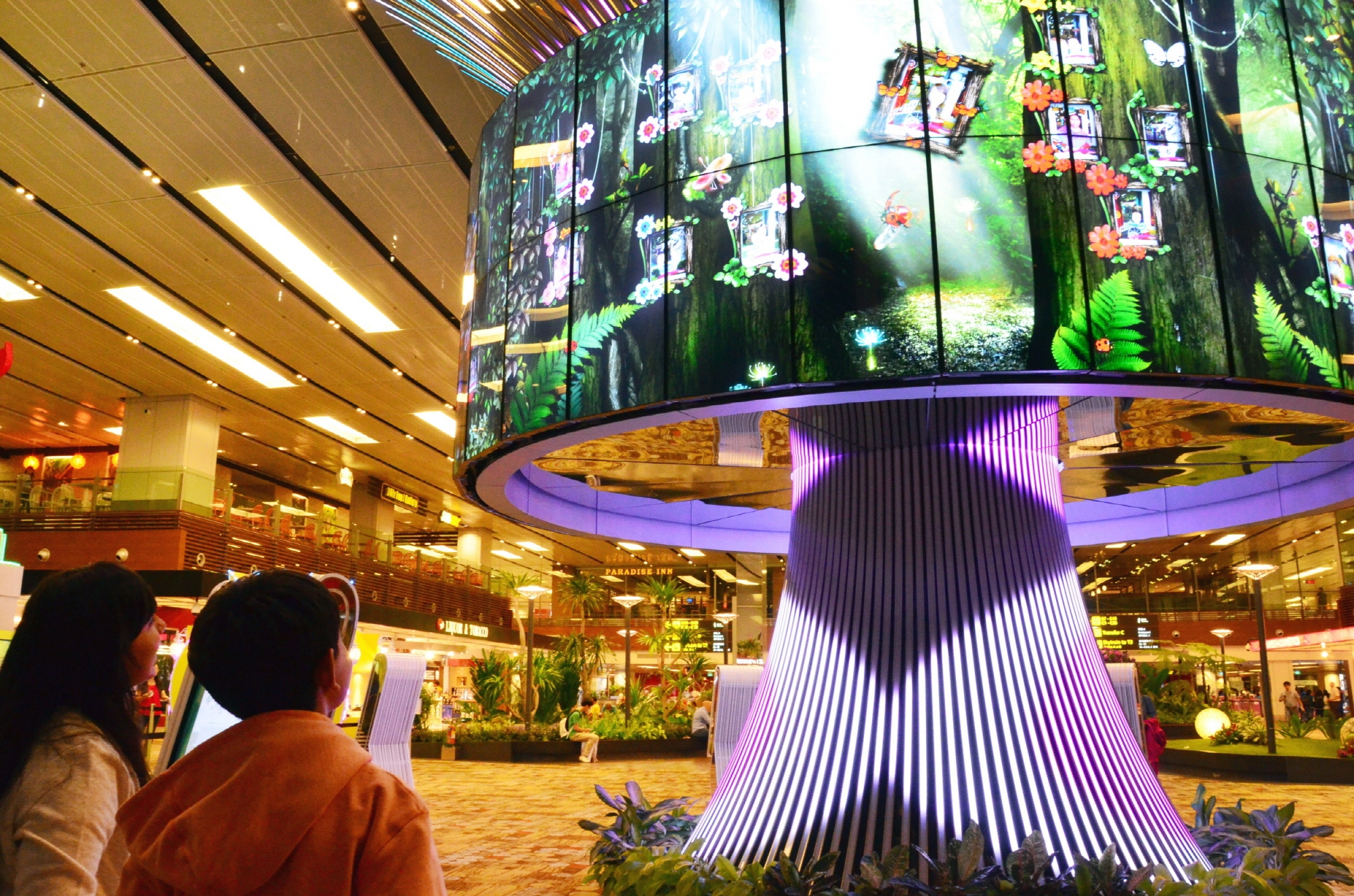 Travelers watch the vivid imagery of LG's 64 47WV30 displays within the Social Tree installation at Changi Airport's Terminal One