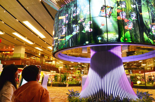 Travelers watch the vivid imagery of LG's 64 47WV30 displays within the Social Tree installation at Changi Airport's Terminal One.