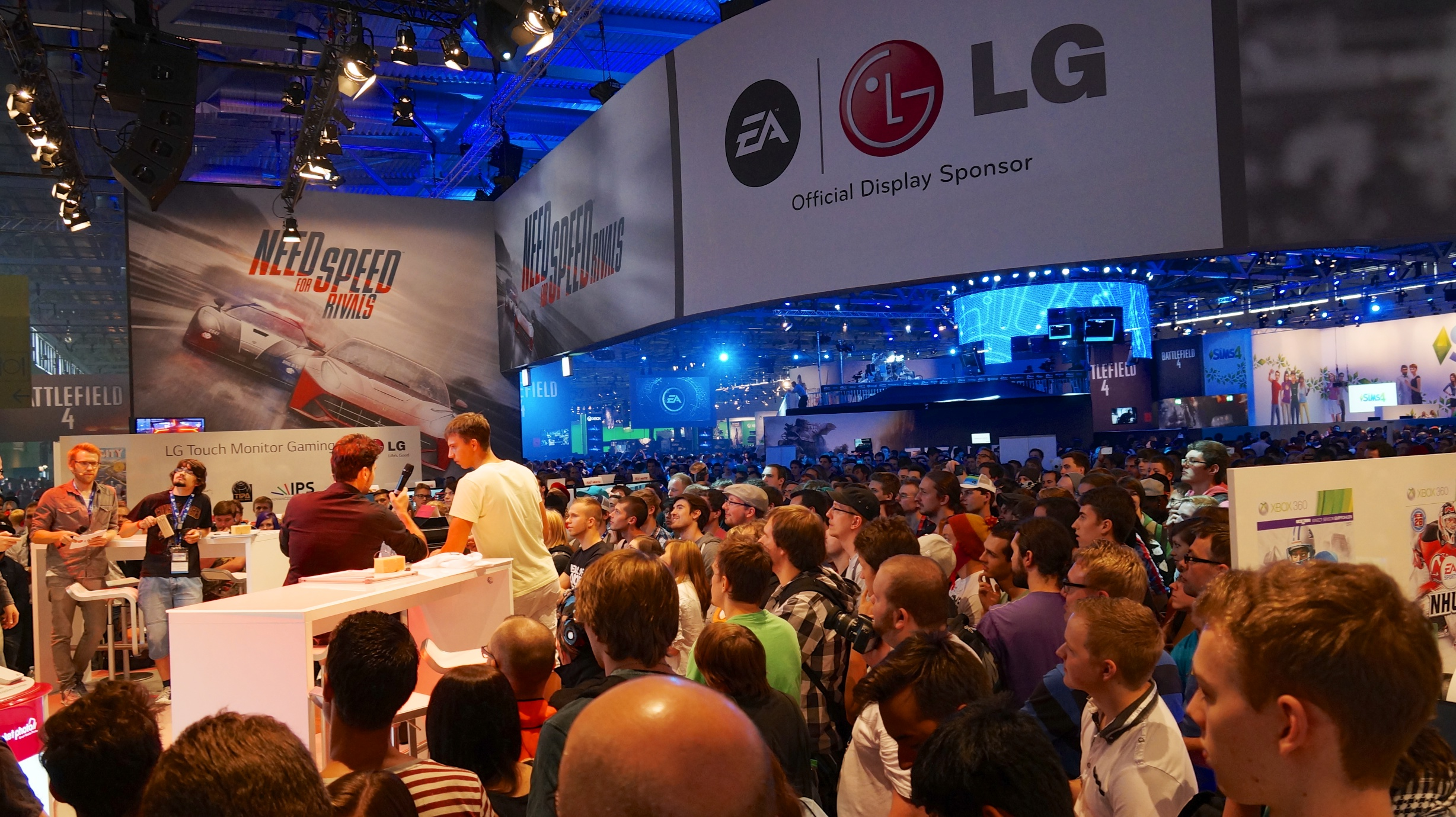 Staff at LG and EA's stage interview a visitor while others watch on at Gamescom 2013