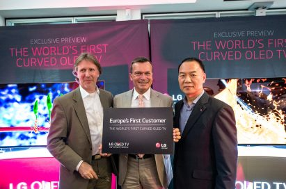 An LG representative and two German market representatives posing for the camera at the exclusive preview of the world's first curved OLED TV.