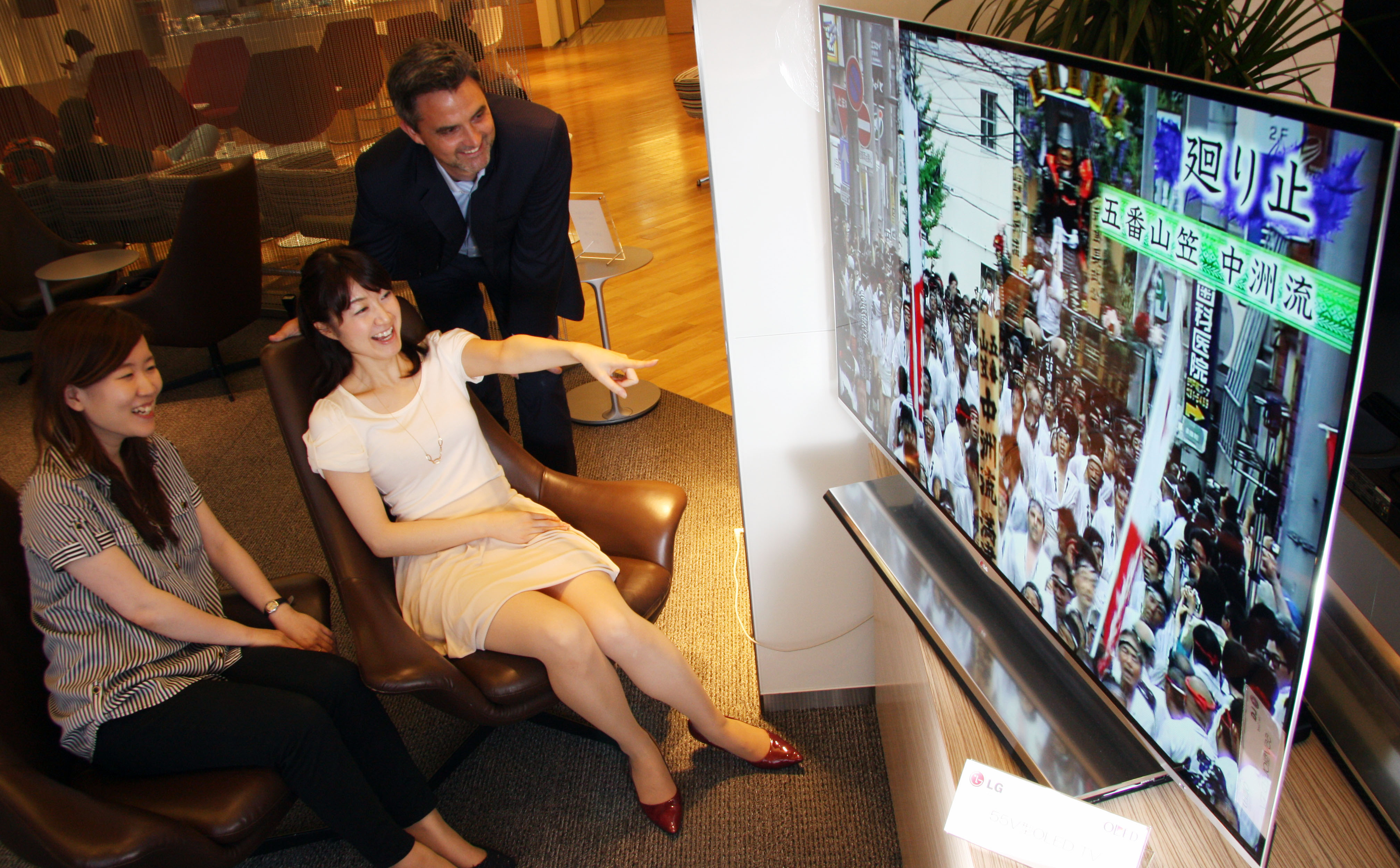 Three travelers enjoy the LG 55-inch OLED TV's incredible display in an airport lounge