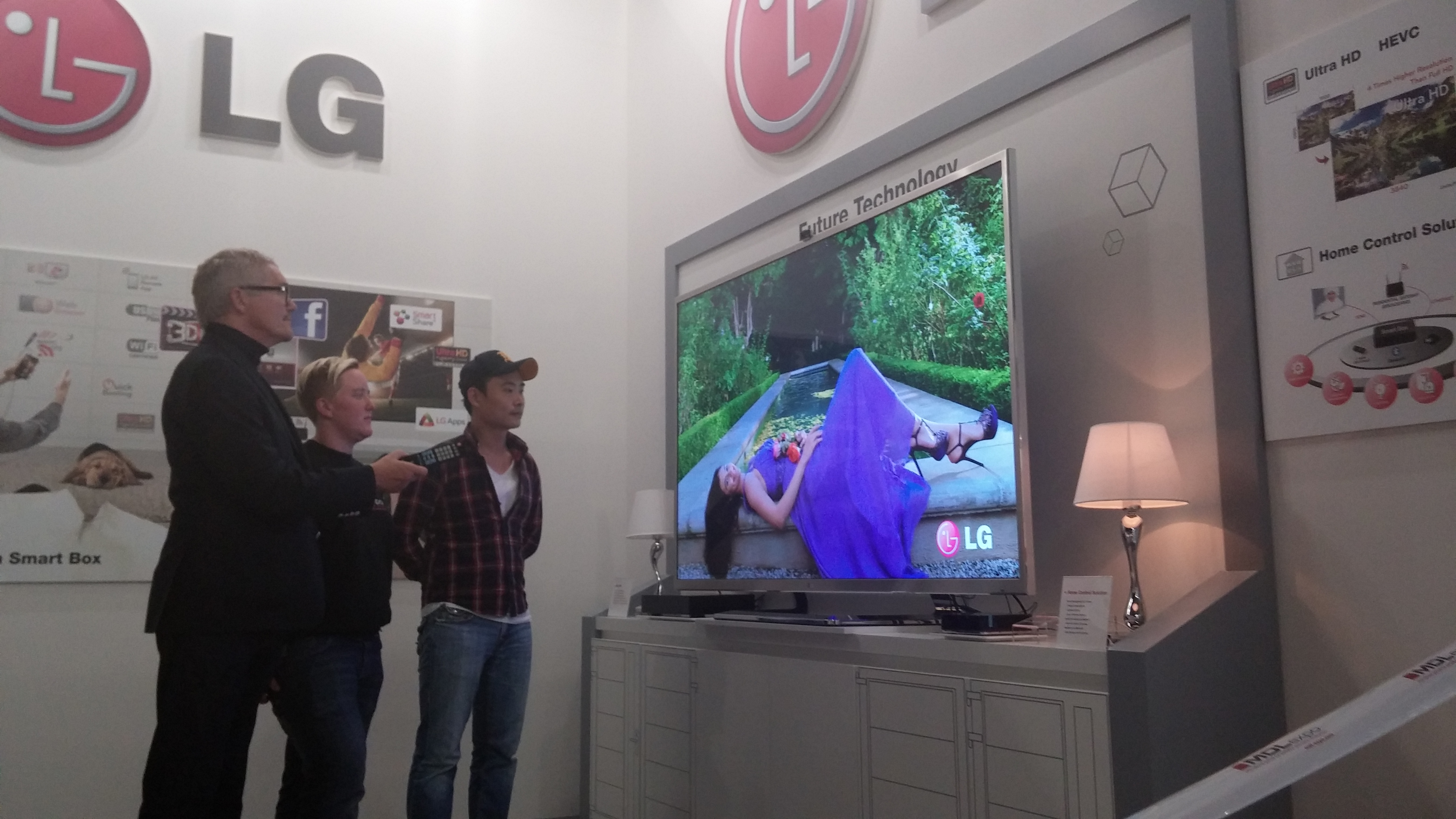 Three visitors watching LG's comprehensive lineup of set-top boxes in LG's International Broadcasting Convention booth