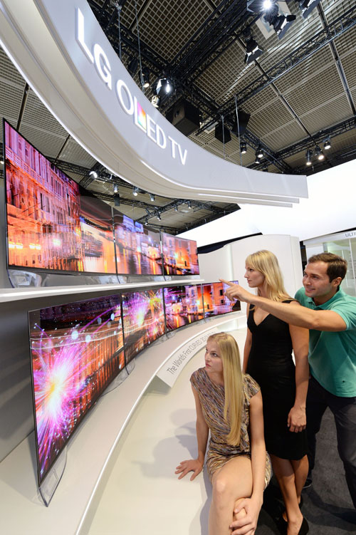 Three visitors view two rows of LG's CURVED OLED TVs on show at IFA 2013.