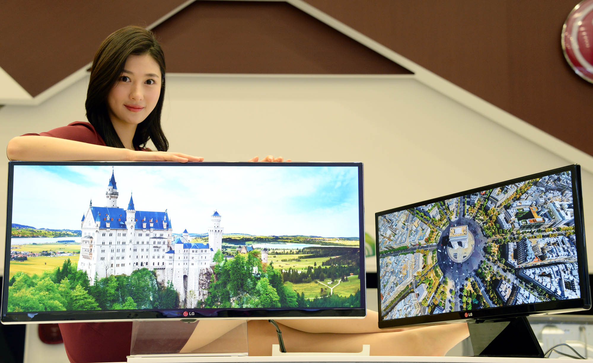 A model presenting the 34-inch and 29-inch IPS 21:9 UltraWide monitors while leaning on the 34-inch model