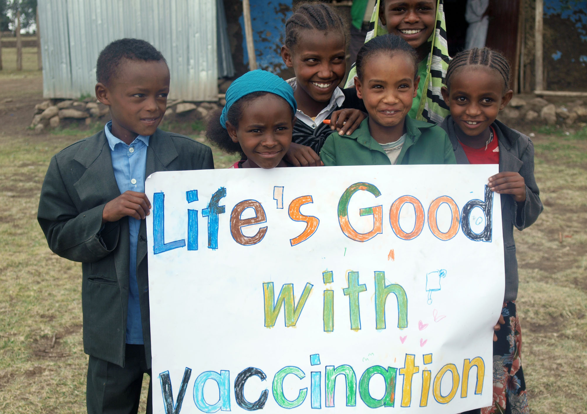 """Children hold a """"Life's Good with vaccination"""" sign together with smiles."""