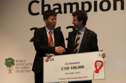 An LG representative shakes hands with a gentleman from the United Nations World Food Programme (WFP) while holding a panel showing LG's donation of 100,00 USD at the LG Home Chef Championship 2013