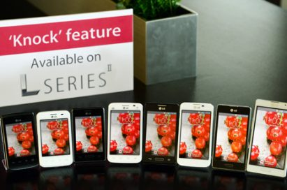"""A panel saying """"'Knock' feature Available on SERIES"""" is standing on a table in front of various LG smartphones."""