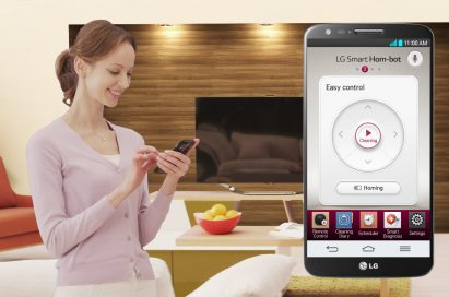 A woman using her phone to remotely control LG HOM-BOT