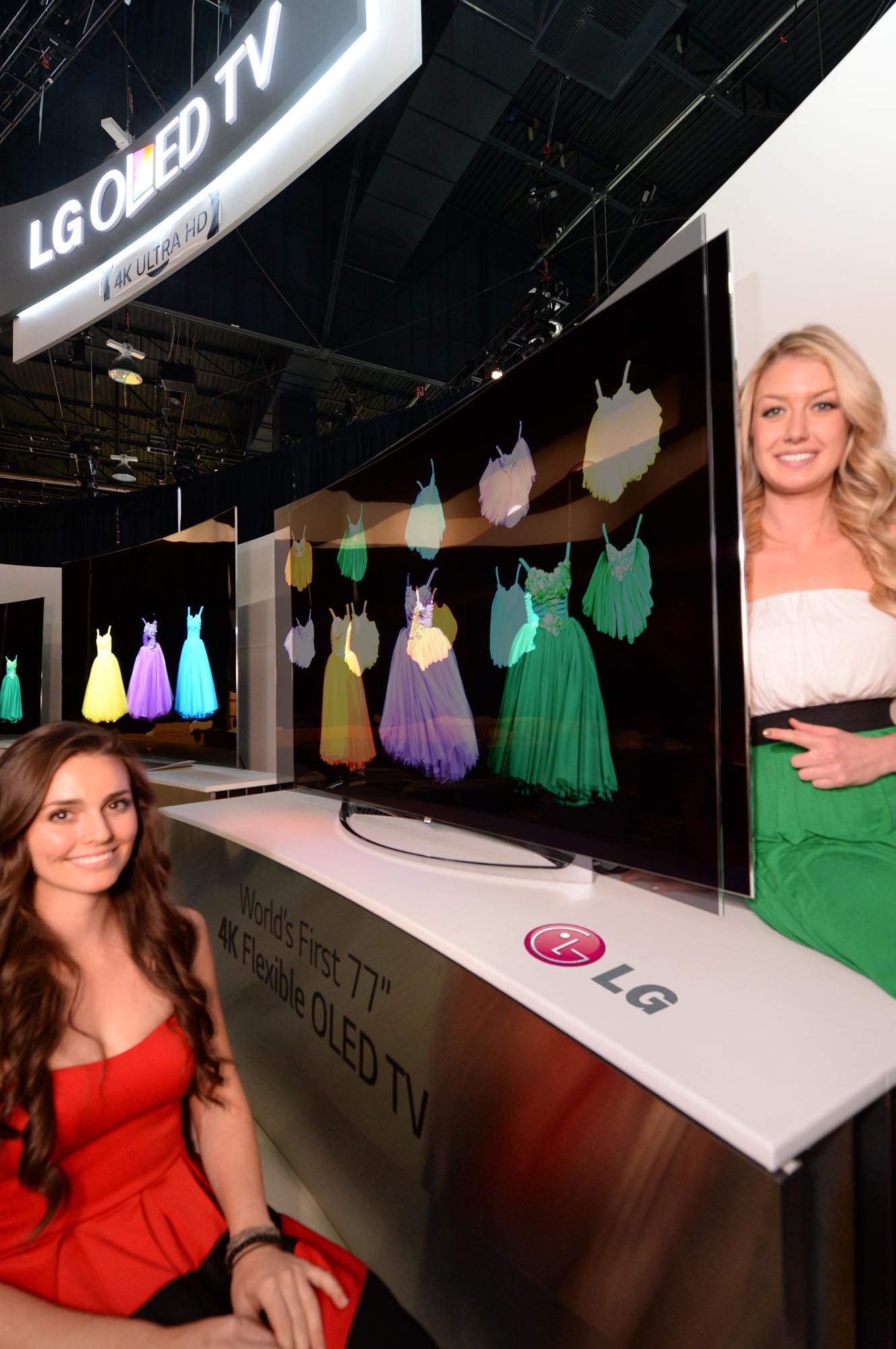 Two models showcasing the world's first Flexible OLED TV by LG at CES 2014