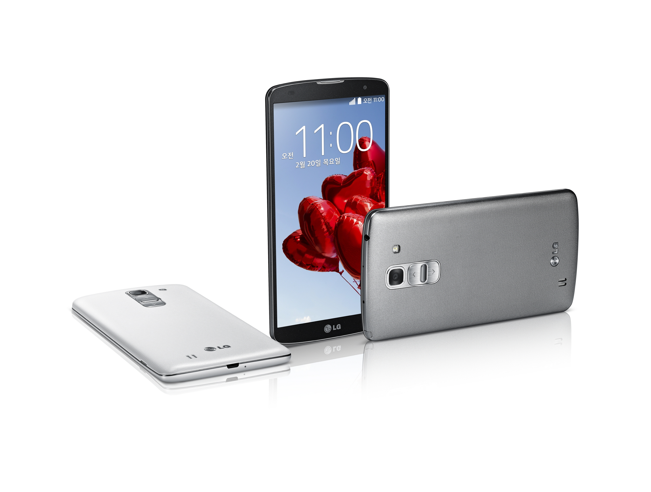 From left to right; The LG G Pro 2 in white face down, in Titan Black color standing upright, and in silver lying on its side.