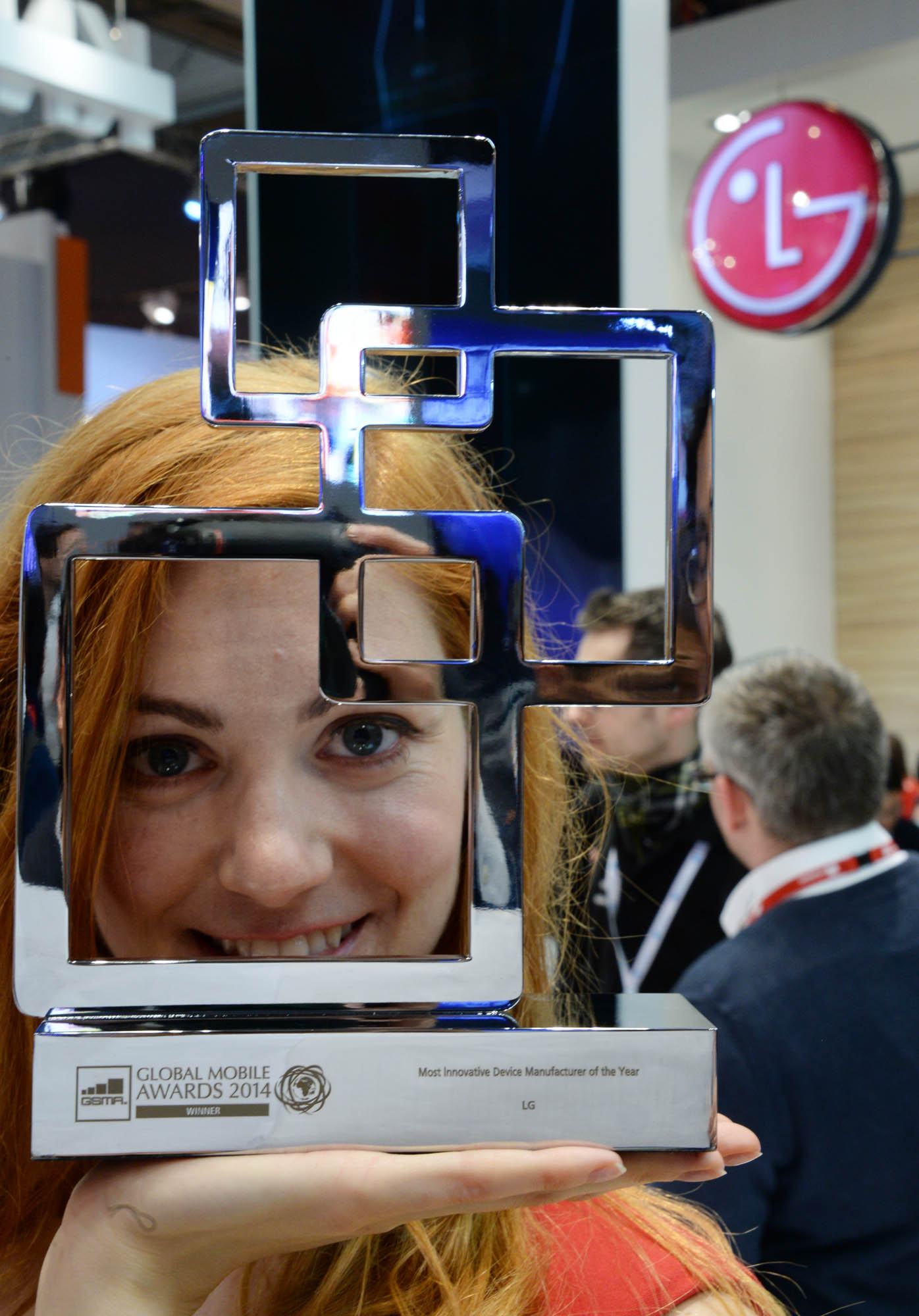 A female model is holding the trophy of the 'Most Innovative Device Manufacturer of the Year' by the GSMA at Mobile World Congress 2014.