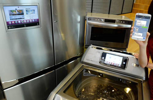 LG's smart appliances including its Multi-Door refrigerator, top-load washing machine and light wave oven, with a model holding a smartphone with the LG HomeChat™ application open.