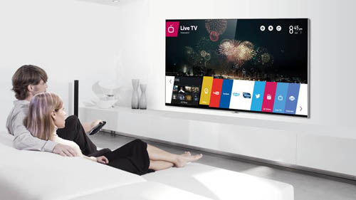 A man and woman sit on their sofa while selecting apps run by webOS with a remote on the LG Smart+ TV.