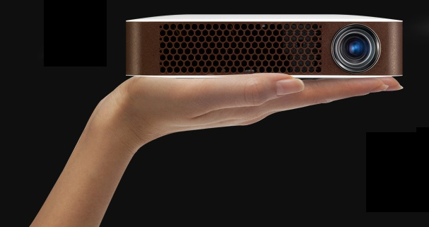 A model holds LG's bluetooth MiniBeam projector with one hand to prove mobility of the product.