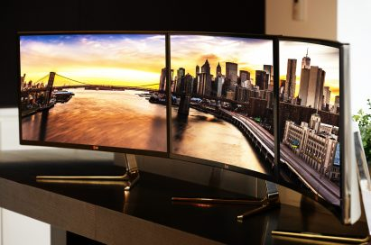 Three LG Curved Ultrawide Monitors 34UC97 put together on a desk to create one giant screen